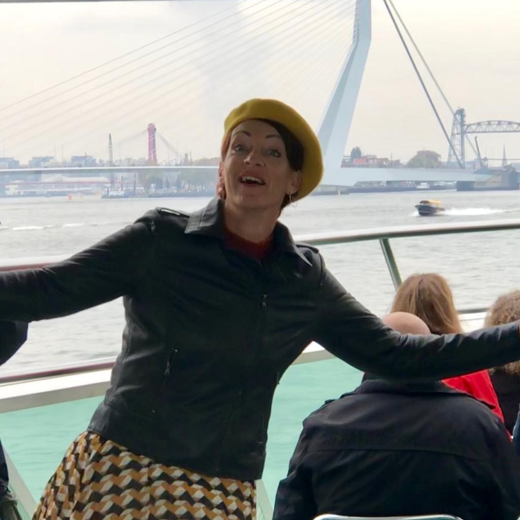 Poserend voor de Erasmusbrug met mijn gele baret en geel gekleurde plissërok. (Als ik mijn rok zo zie denk ik dat de ontwerper zijn inspiratie vond in de kubuswoningen van Rotterdam...moet haast wel.)